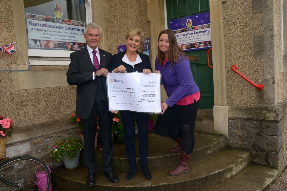 Past President Ian Ramus of Taunton Rotary Club presenting a cheque for 'Archie', to the patron Angela Rippon CBE, alongside the Manager, Emma Green of Reminiscence Learning.