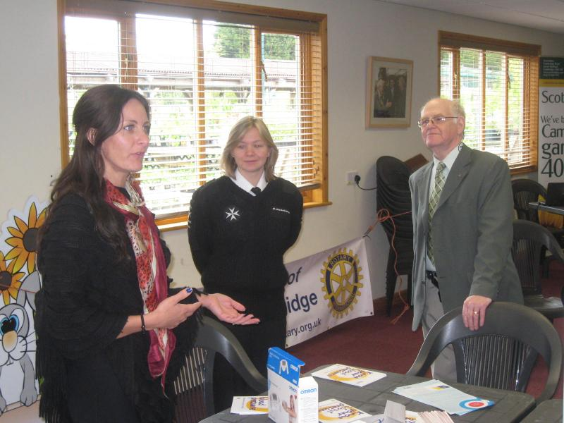 Vicky from OMRON and Lucie from St Johns Ambulance talk with John(Rotary).