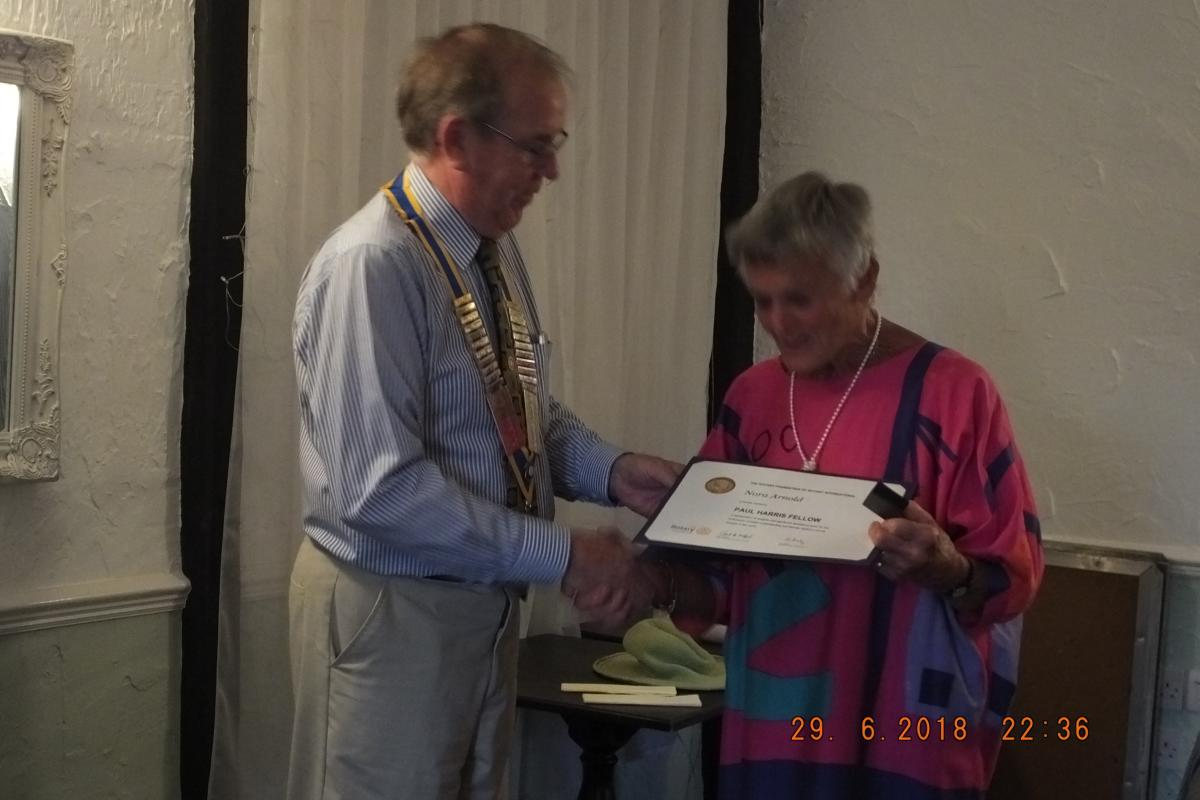 Outgoing President Robin presents a Paul Harris award to Nora Arnold