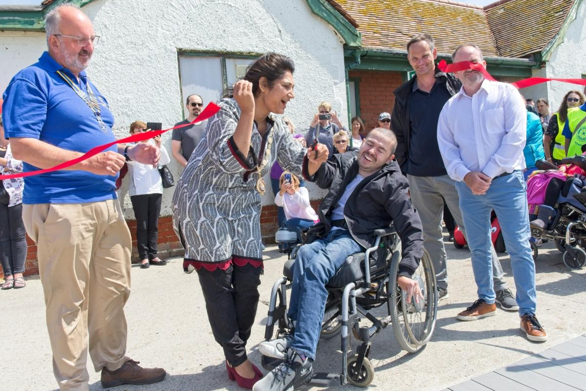 Sam Taylor with Mayor Cllr Nazish Adil cuts the ribbon to open Seaford Beach access with Rotarian Rodney Reed looking on.