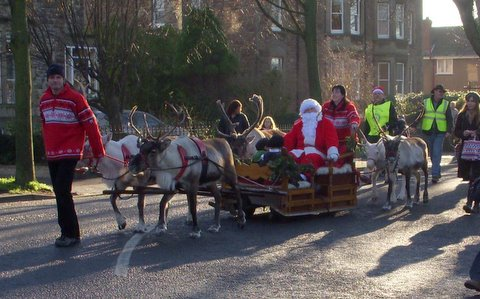 Reindeer sled and Father Christmas with prizewinners starting the Parade