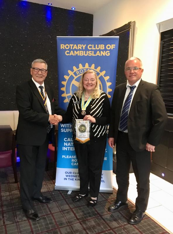 President Robert Dickie and incoming president Kenny Finnie present ADG Margaret Morton with a 50th anniversary banner.