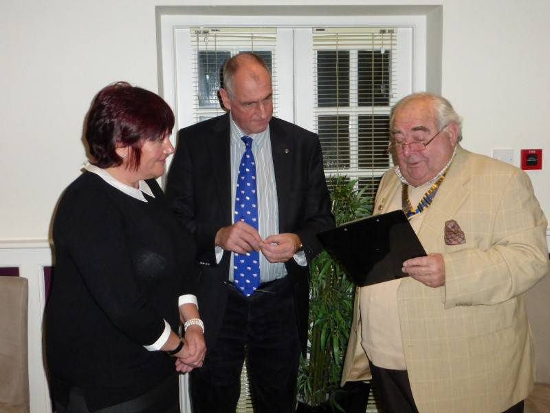 Another two new members! - Sponsor Tim Raw fixes Rotary badge for new Rotarian Juliet Raw