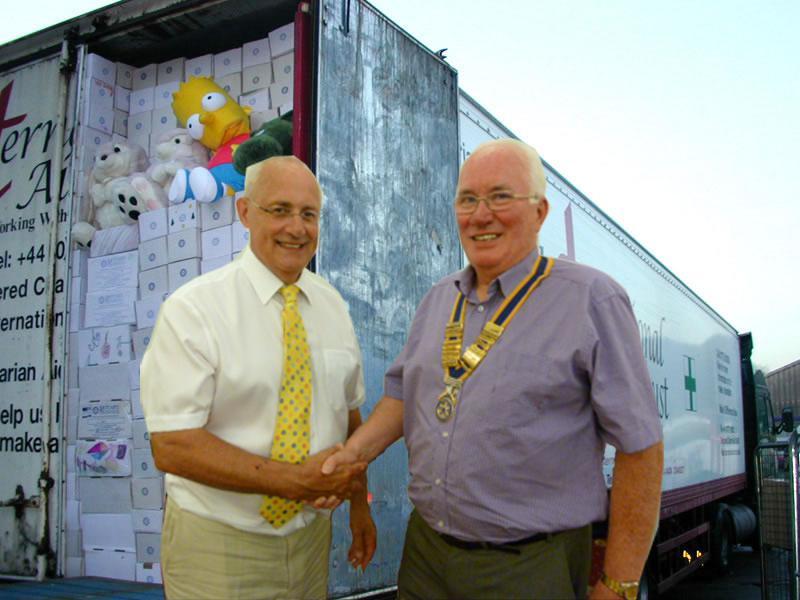 Rotarian Jim Houghton and President of the Rotary Club of Southport Links Bill Thomas, with a lorry load of shoeboxes (and Bart Simpson)