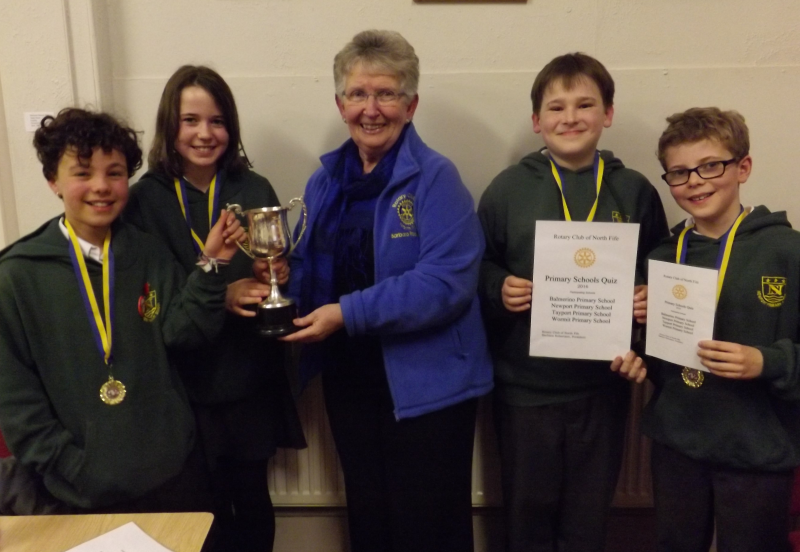 President Barbara Robertson of the Rotary Club of North Fife seen here presenting the winner's trophy to Newport Primary School's triumphant P7 quiz team.