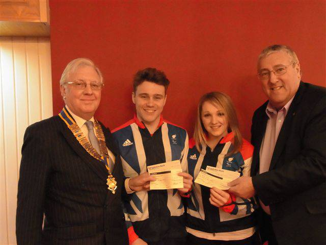 picture shows Rotary President John Whiteley, left, and Armchair Club member Stewart Rickersey, right, flanking Ollie and Charlotte.