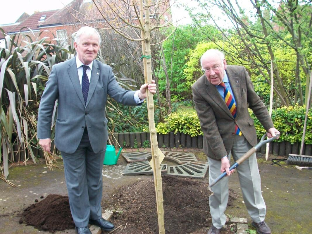 Chris Halliwell (left) , Chairman of the Portsmouth Rotary Housing Association assisting  David Collins, our Club President for the Centenary Year, planting a tree at Harrison House.at Stamshaw.