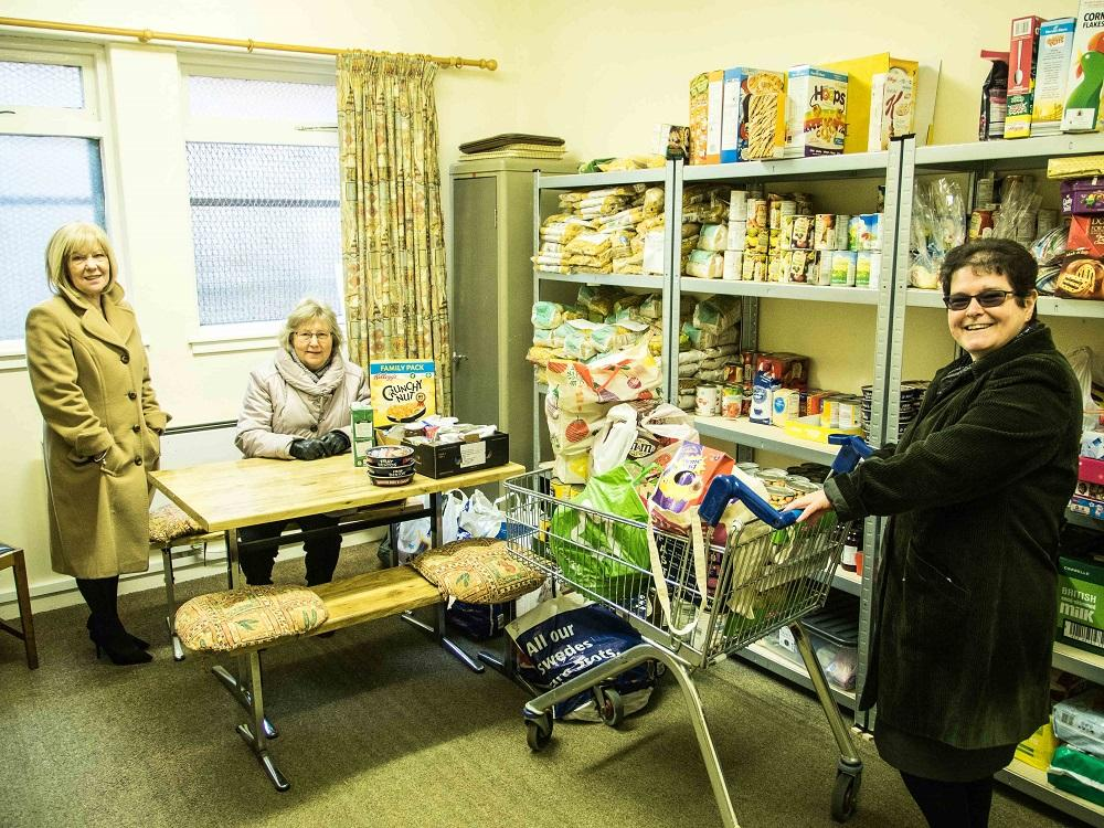 Rotarians donate to the URC Food Angel Foodbank - With the donations delivered to the Food Angels,  Betty and Elma lend a helping hand to  Rev. Branwen to restock the shelves.