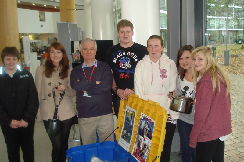 Students at South Cheshire College with President Jerry Park discussing Life Aid Boxes