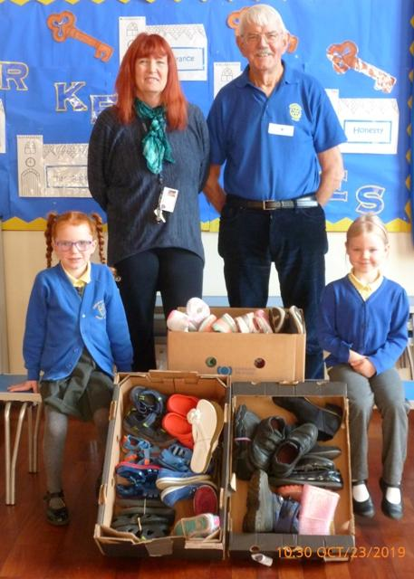 Headteacher Caroline Sibson and School Governor Robert Mirfield with two of the pupils who brought shoes