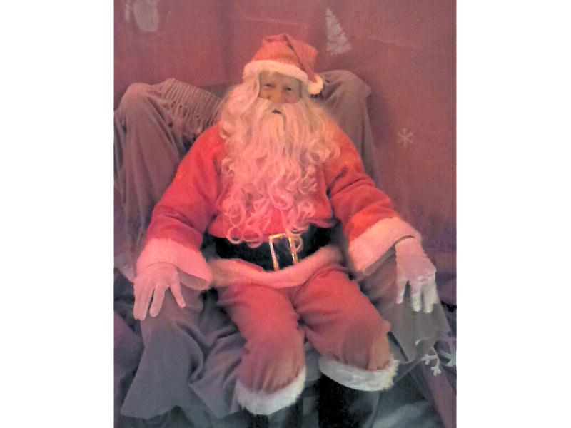 Santa waits in his grotto for the first brave kiddie  .  .  .