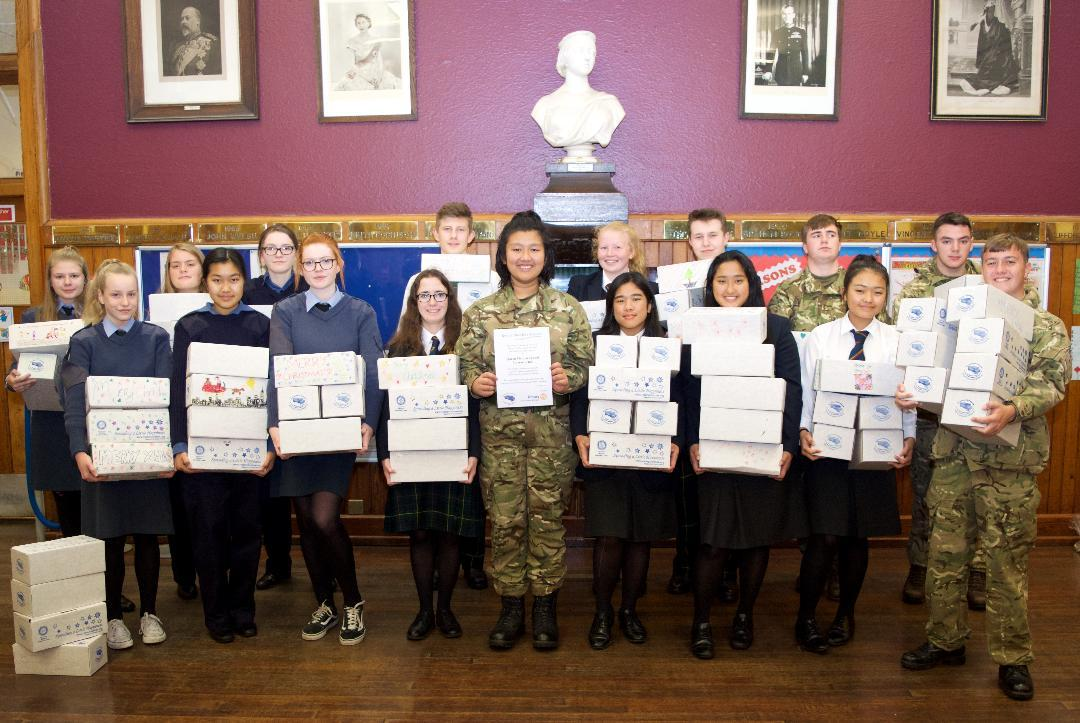 Rotary Shoeboxes 2018 - Interactors (Junior Rotarians) from Queen Victoria School in uniforms of the three armed services in the cadet force, together with civilian members, carrying their collection of shoeboxes