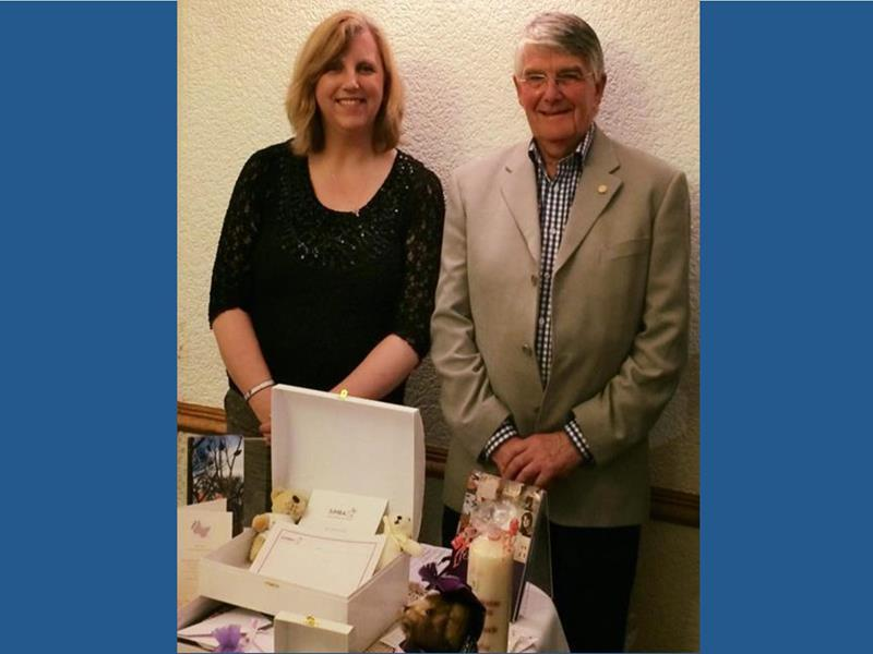 Susan Simpson with President Bruce Robertson and a display of items provided by SiMBA to bereaved families after the  loss of a child
