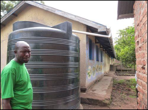 Mr Francis Olowo, deputy Head teacher, with the water tank and the 40 m of guttering used to fill it