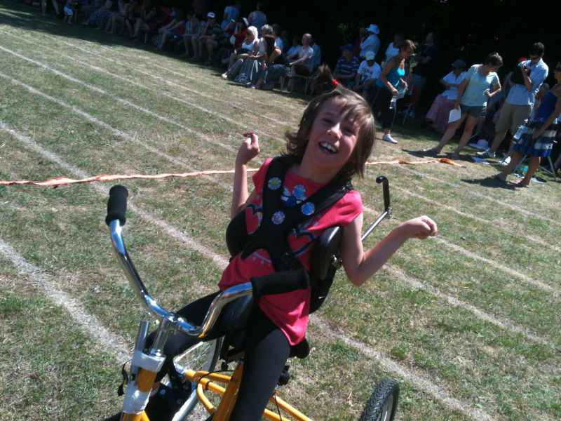 19 July 2013: Tamsin shows her delight in crossing the finishing line at Stockham School's Sports Day astride her special tricycle, provided with help from the Rotary Club of Wantage, and others.