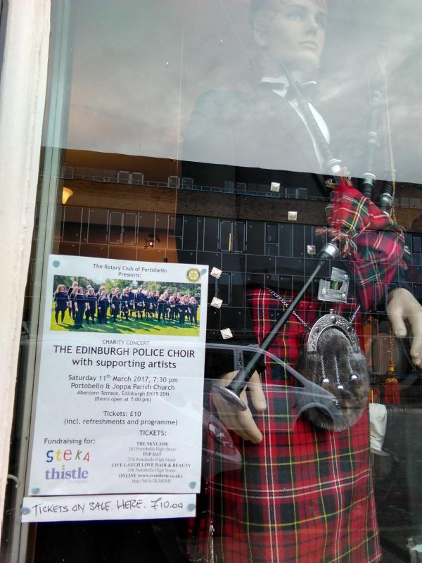 Concert poster in the window of Top Hat - the place to go for top class kilts.