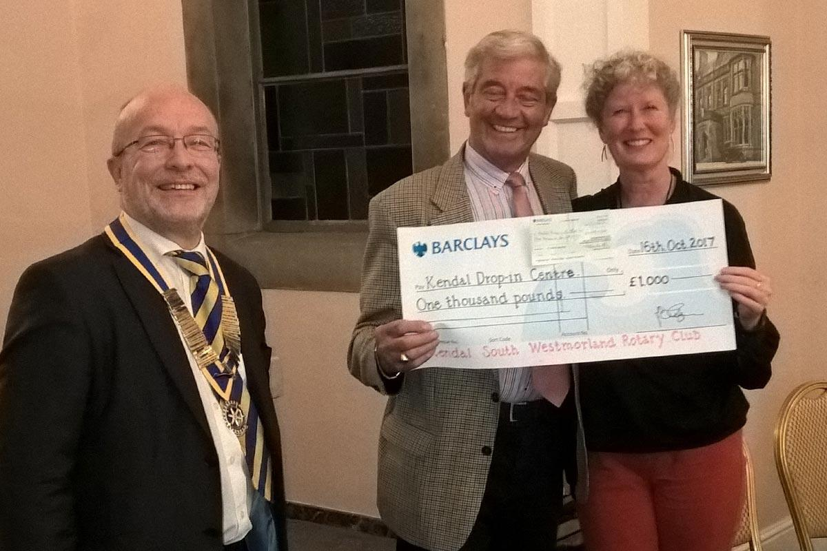 Phil presenting cheque to Shirley Gilpin from Kendal Drop In Centre, accompanied by Mike Trelogan
