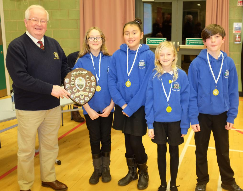 Club President Colin Mackenzie presents the 2019 trophy to the team from Dairsie Primary School
