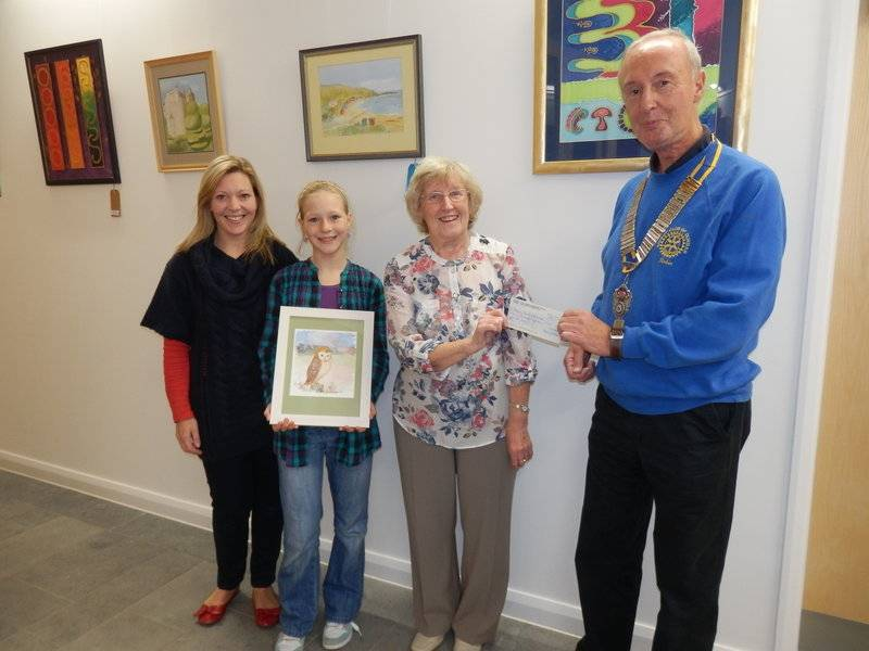 Local artist, Anne Jackson presents a cheque for £415 to Dunbar Rotary Club President Robin Hamilton at Dunbar's new Community Centre. L to R.  Successful bidders Nicola and Emma Lonie, Anne Jackson and Robin Hamilton.