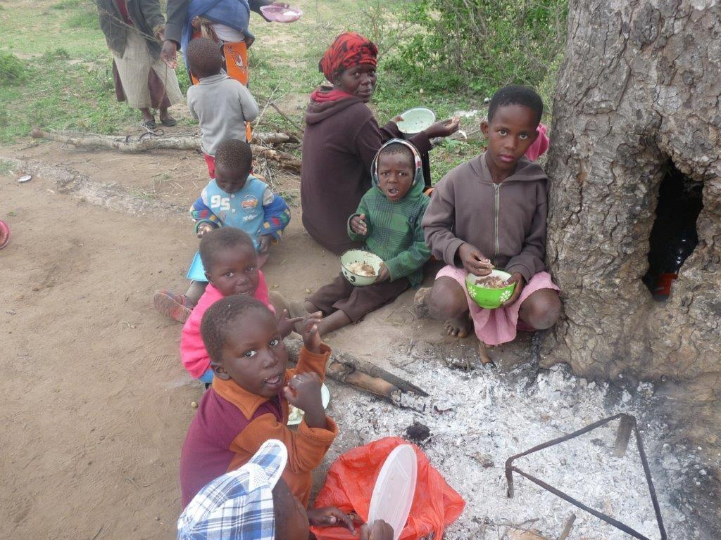 Children eating under a tree