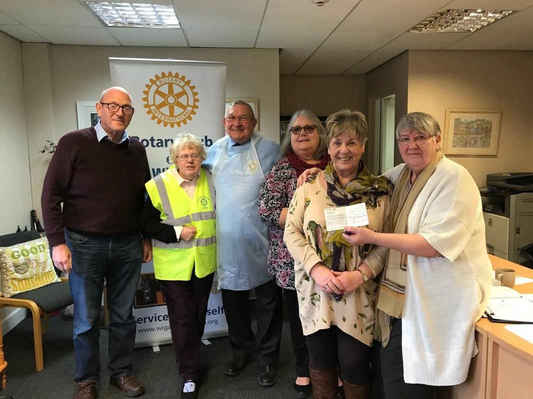 Picture of Barbara Nettleton receiving a cheque from Wigan Rotary Club.
