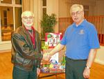 COMMUNITY, INTERNATIONAL & YOUTH - Chairman of SMRC Projects, Rtn. Jim Austin presents food parcels to Chairman of Waves, Richard Plowman.