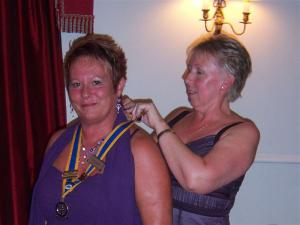 Outgoing President Barbara places the jewel around incoming President Philippa's neck