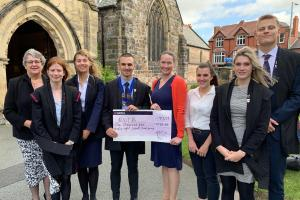 Interact pupils present £1,100 to the Royal National Institute of Blind People