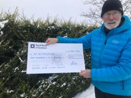 Member, Tony Burley, with cheque before handover.