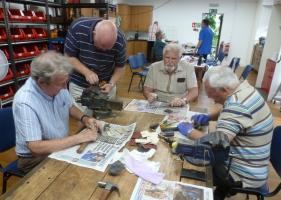 Members of the Rotary Club of Barton-le-Clay help refurbish old tools.