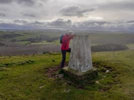 Pat Sutherland at a triangulation pillar or 'trig point'