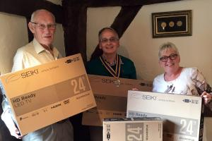 President Ian Haigh and John Neave handover the TVs to Jools Payne