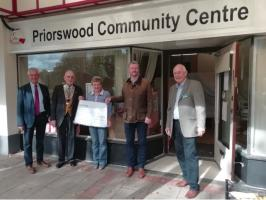 Priorswood Community Centre Manager, Lesley receiving a cheque from President Peter Ball