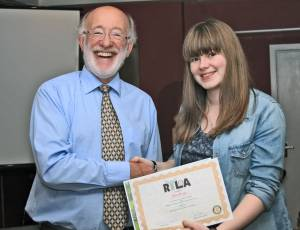 Erin is presented with her RYLA group picture and a certificate by Club President Gordon Sanders