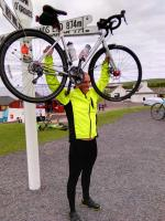 Daniel brandishing the bike up high, in jubiliation at having finally reached John O'Groats.