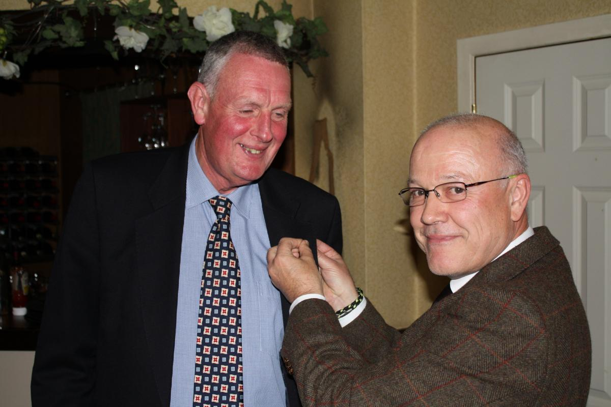 President Trevor Baxter welcomes new Rotarian Alan Nisbet into the club