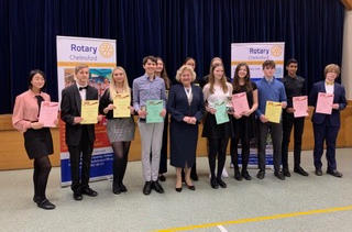 A row of young people holding certificates with a middle-aged woman in the middle