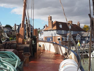 Looking over the bow of a sailing barge towards houses on a quayside
