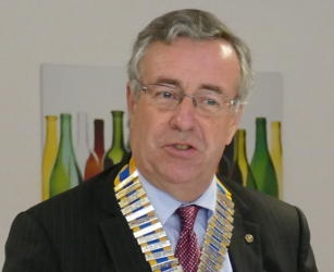 A man wearing glasses and a chain of office