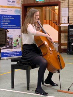 A long-haired young woman playing a cello