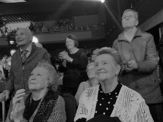 Black and white photo of senior citizens enthusiastic about a theatrical performance