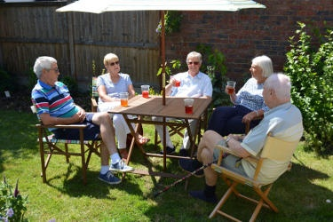 Five people sitting round a garden table