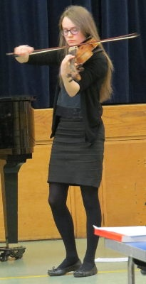 A teenage girl wearing glasses playing a viola