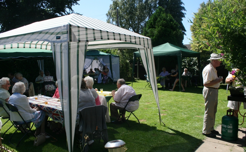 Local senior citizens enjoy a barbeque lunch in a member's garden.