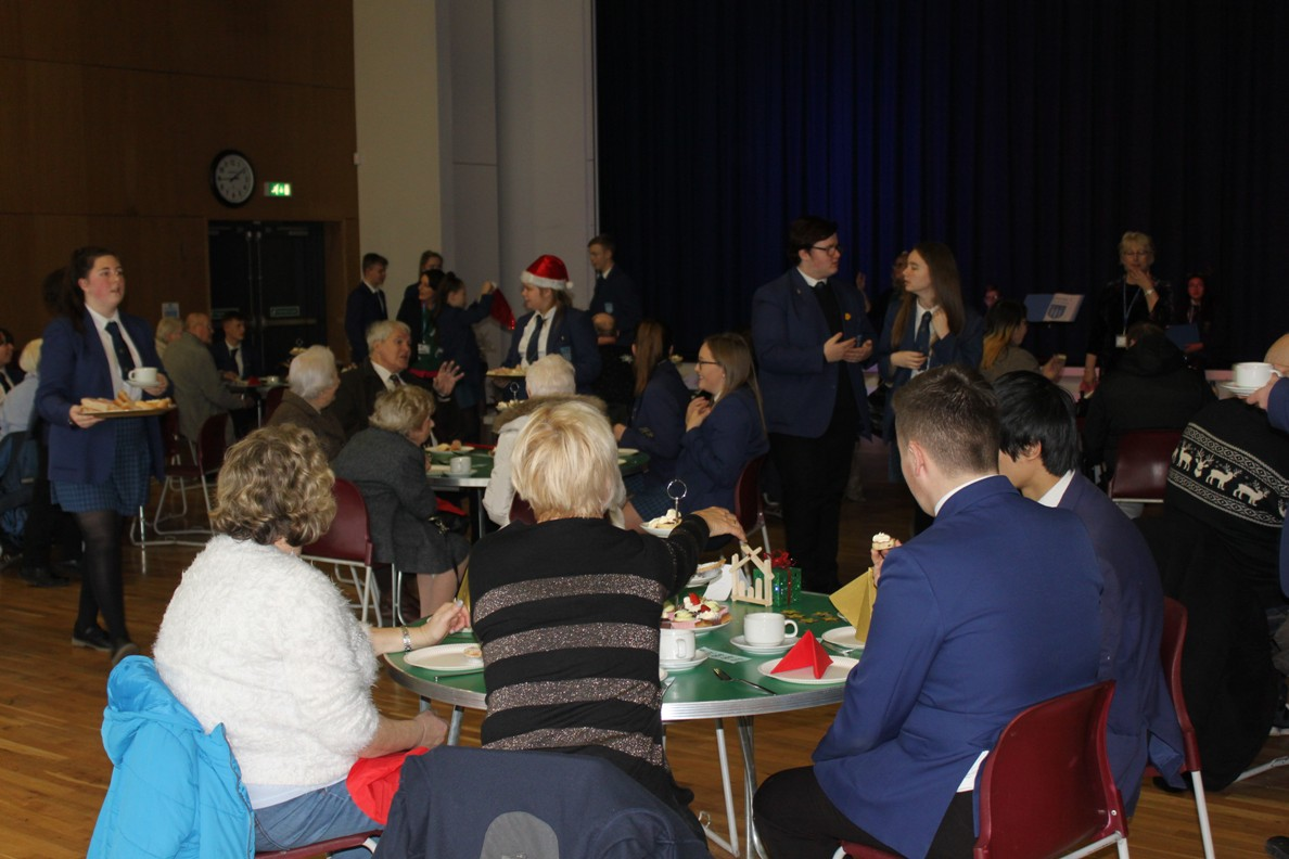 Highfield Leadership Academy Christmas Tea Party for elderly residents. - Two students sat on each table to chat to guests.