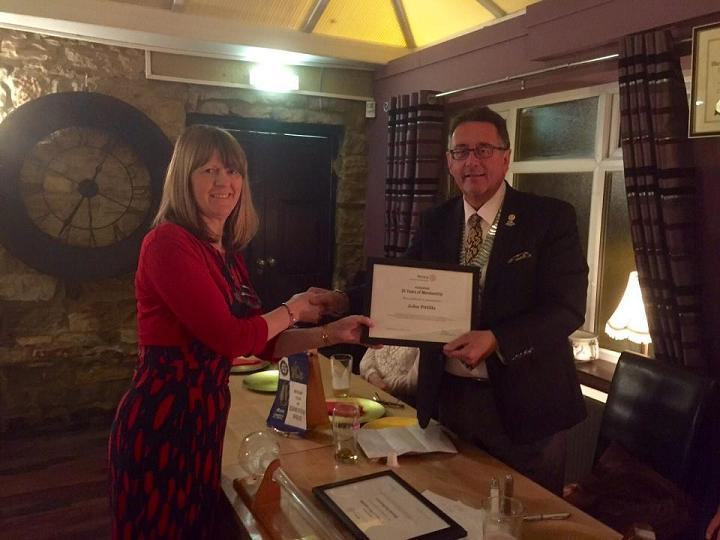 Club 25th Anniversary Meeting - Carol Pittilla accepts the certificate from DG Terry on behalf of John Pittilla to acknowledge his 25 years membership of Rotary