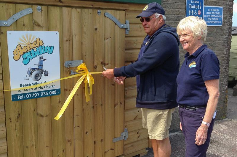 BeachAbility  - President Ray cutting the ribbon watched by Margaret Le Herrisier the founder of BeachAbility in Jersey.