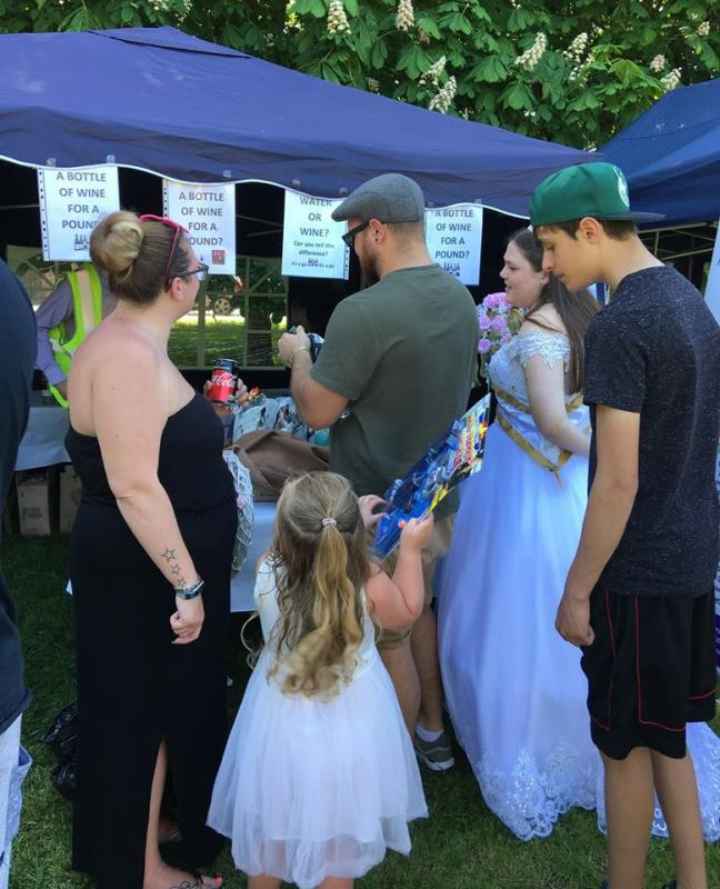£551 RAISED AT THE <br/> 2018 MAY FAYRE - Pictured is the May Queen and her family trying their luck on the Water and Wine stall. The little girl in the foreground is showing the prize she won on the tombola.