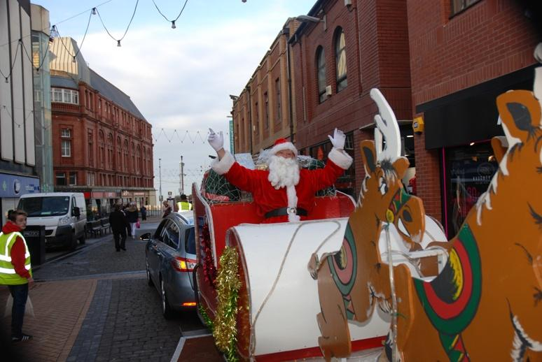 SANTA VISITS THE HOUNDSHILL CENTRE, BLACKPOOL - Santa sat down but was still waving.