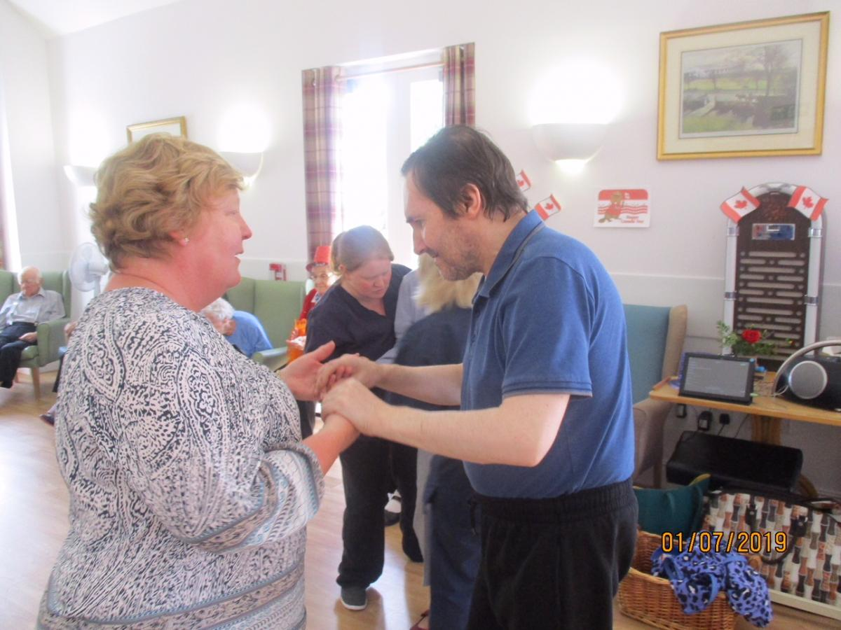 Volunteering in local Care Homes - Rotarian Diane teaches a resident some new moves